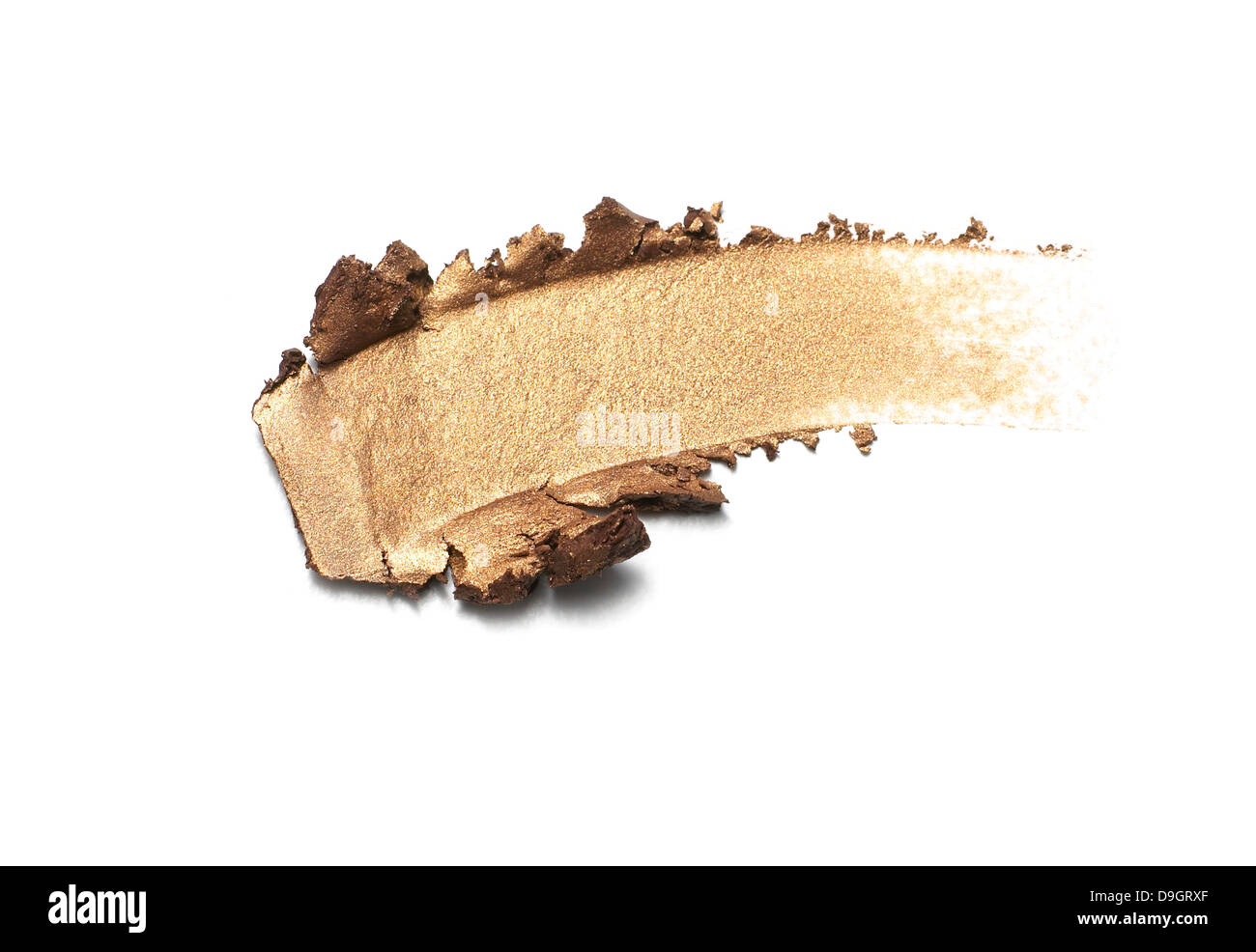 gold shimmer eyeshadow smear cut out onto a white background - Stock Image