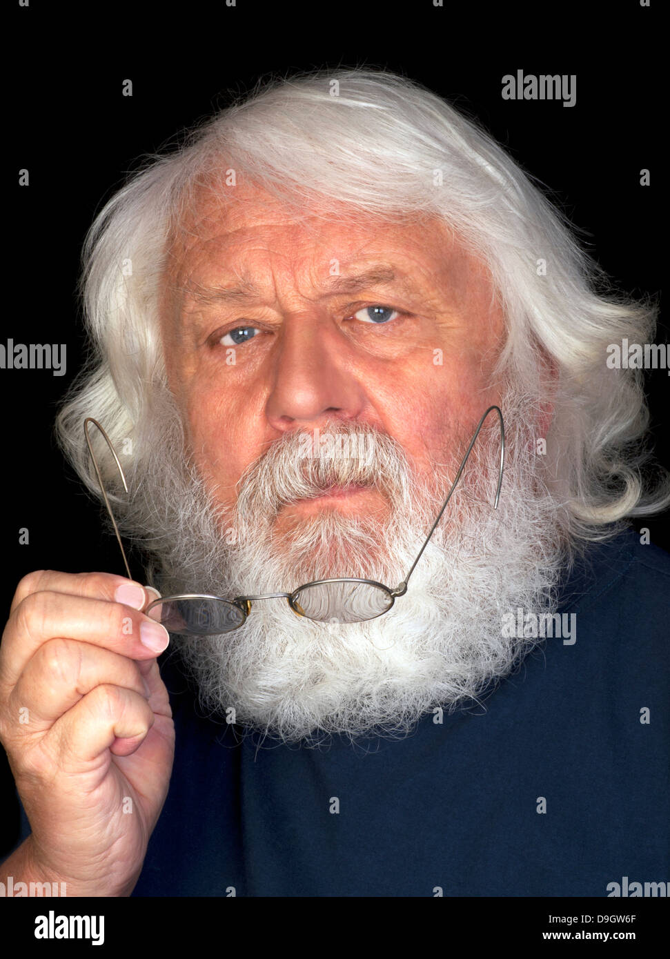 Senior with full beard, thinking with glasses in his hand - Stock Image