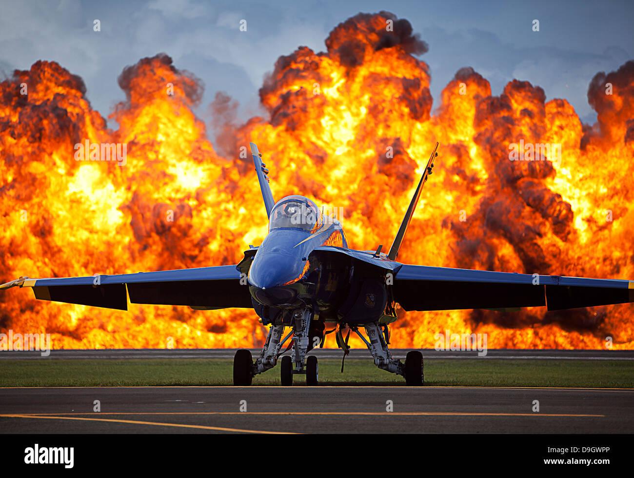 A wall of fire erupts behind a U.S. Navy F/A-18 Hornet aircraft. - Stock Image