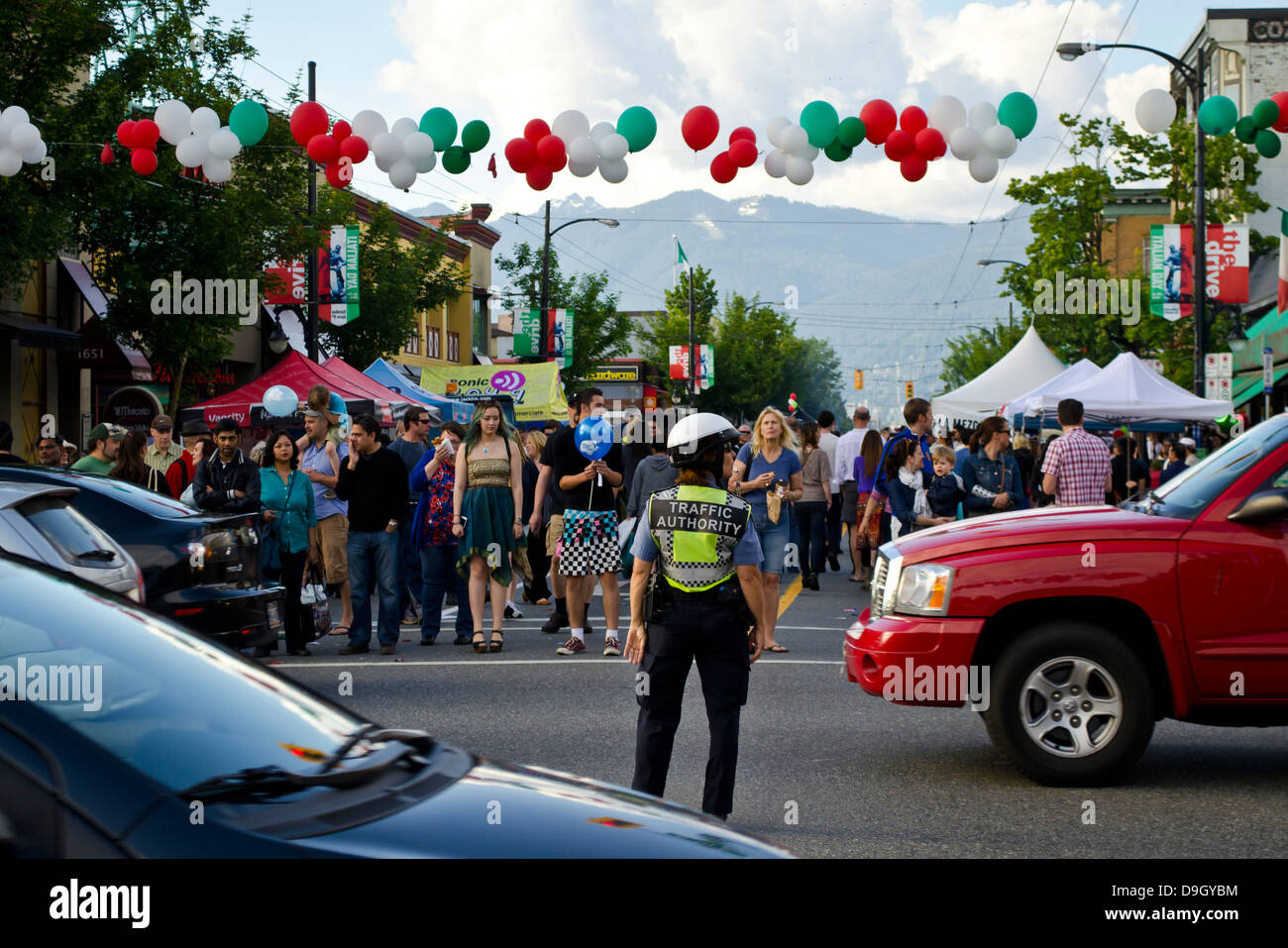 A traffic officer controls busy traffic while the crowd waits to cross the street at Italian Day street festival - Stock Image