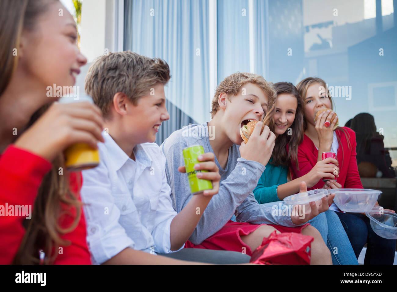Friends enjoying fast food together - Stock Image