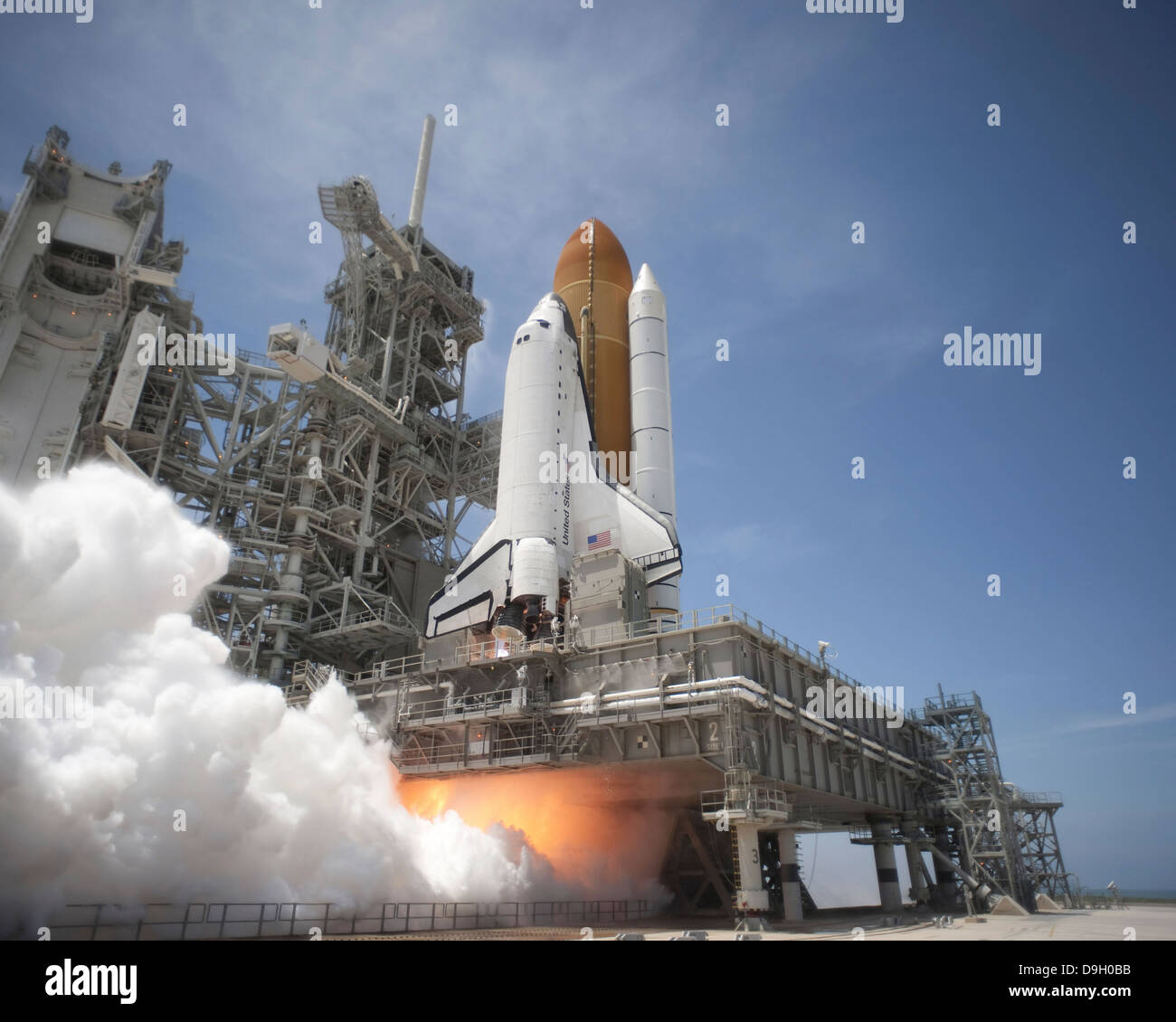 An exhaust plume forms under the mobile launcher platform on Launch Pad 39A as space shuttle Atlantis lifts off - Stock Image