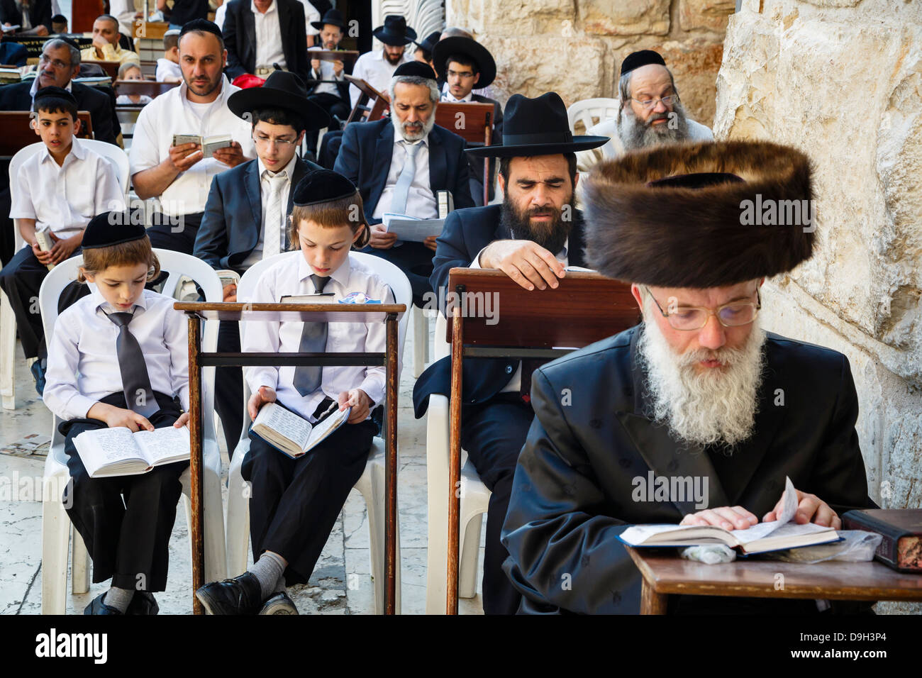Orthodox jewish people praying at a synagogue by the western wall wall (Wailing wall) in the old city, Jerusalem, - Stock Image