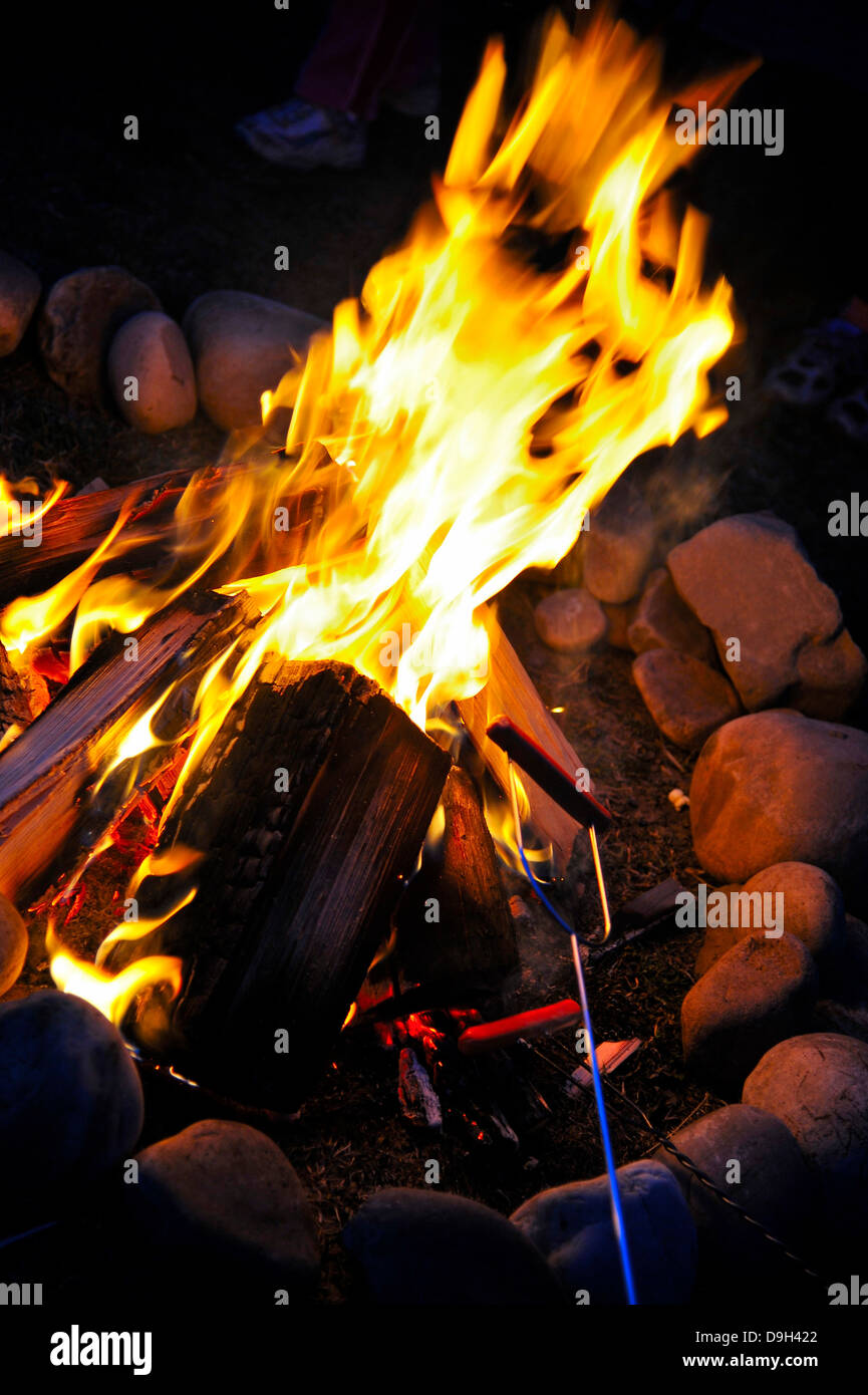 A campfire with yellow flames and a hot dog roasting on a fork. - Stock Image