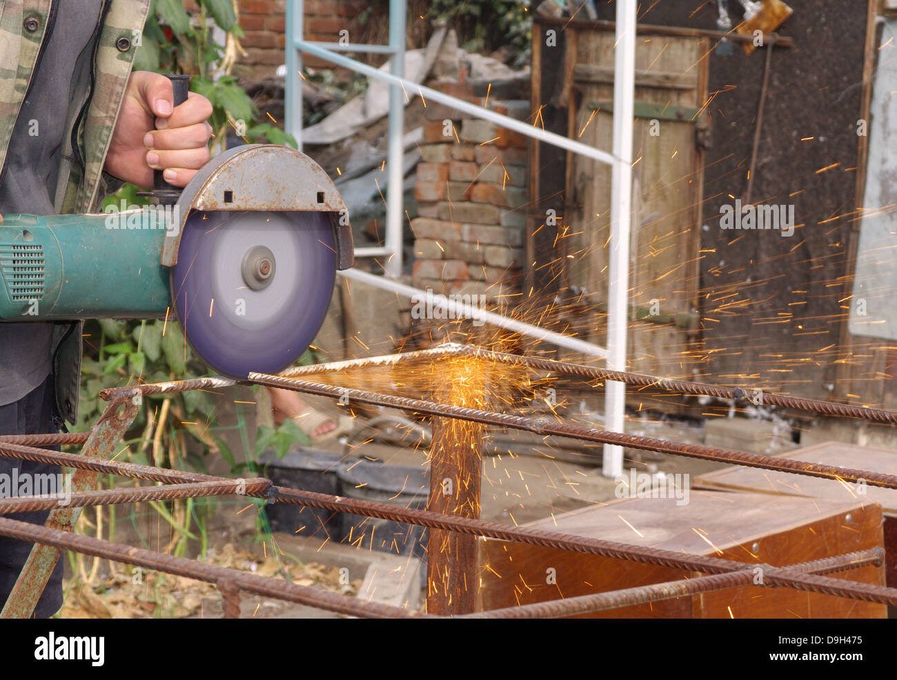 Angle Grinder Metal sawing with flashing sparks close up and Repairman hands home repair garden working summer time - Stock Image
