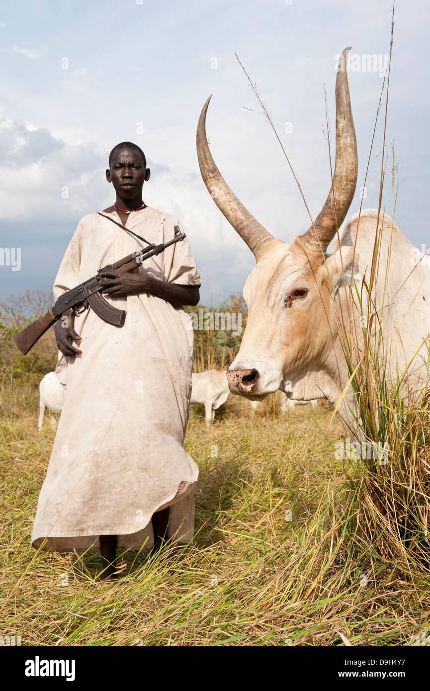 SOUTH SUDAN Lake states, Rumbek , Dinka shepherd protect their cattle with Kalashnikov AK-47 rifle from cattle raider - Stock Image