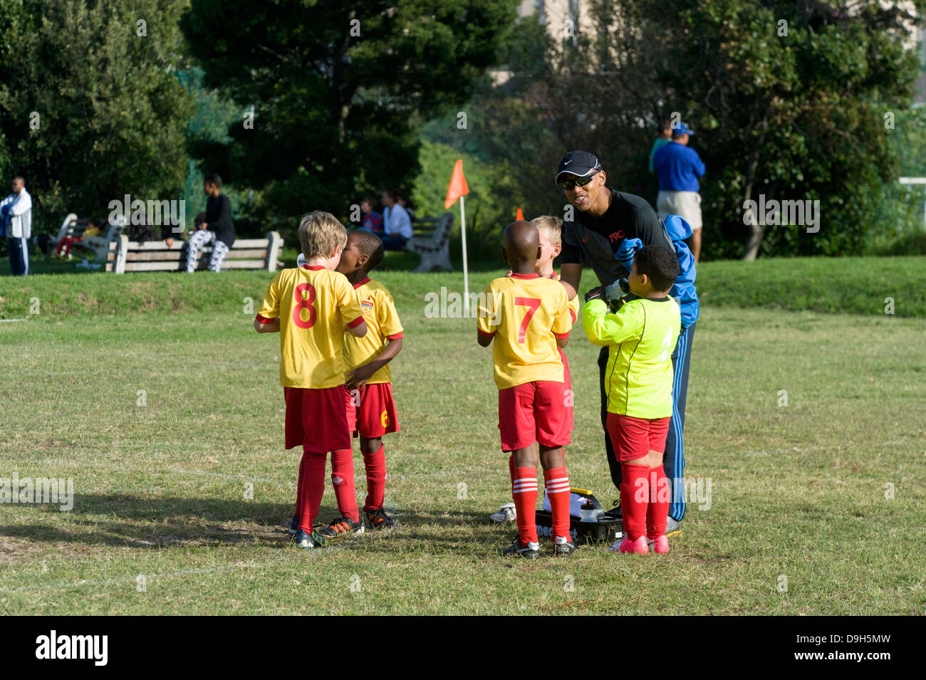Coach instructs junior football player during half time break of a match, Cape Town, South Africa - Stock Image