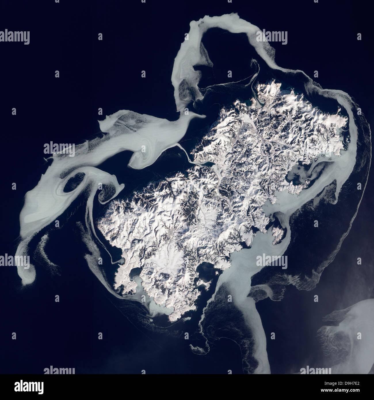 Sea ice surrounds the volcanic island of Shikotan. - Stock Image