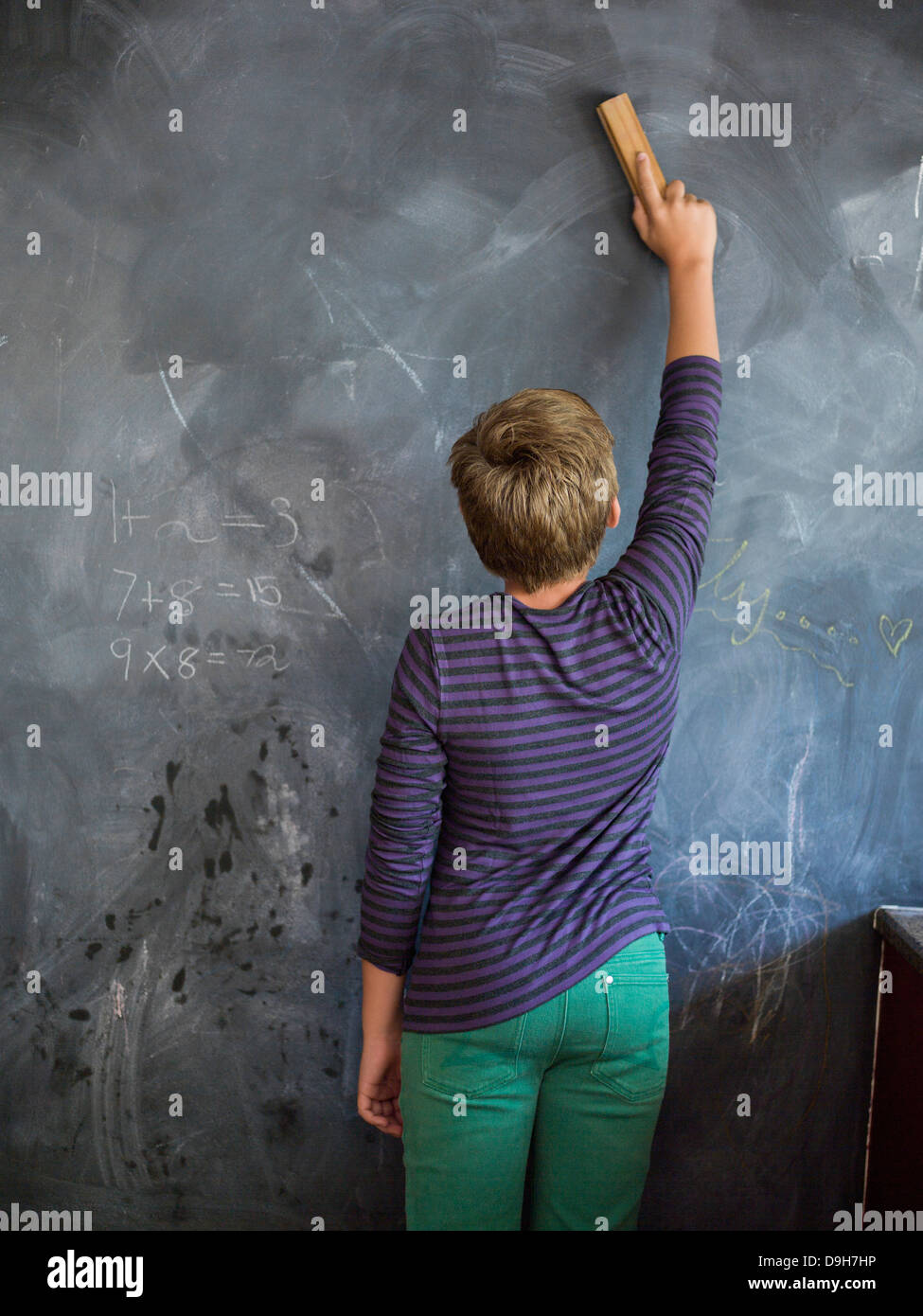 Boy cleaning blackboard with a duster in a classroom - Stock Image