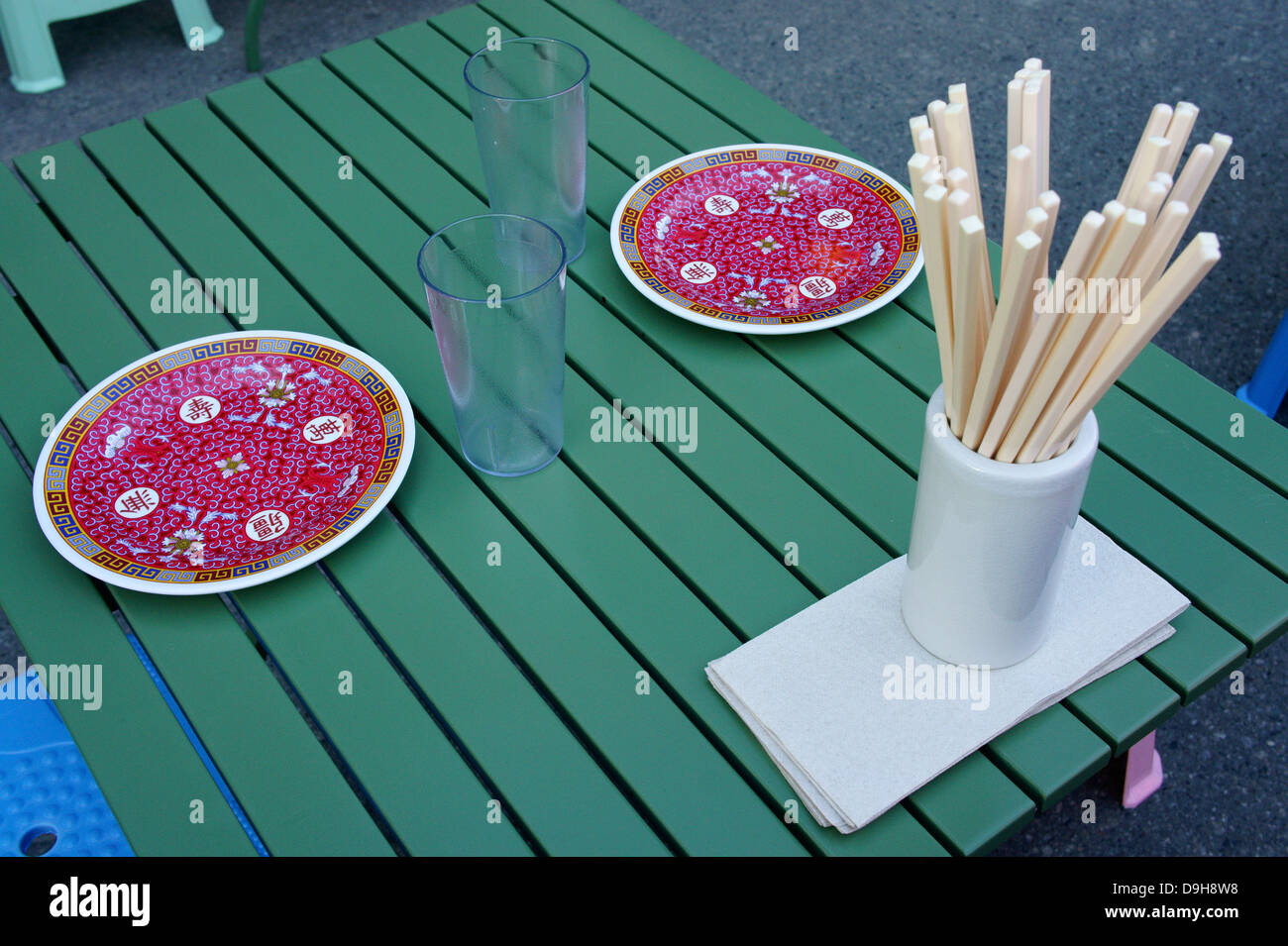 Chinese plates and chopsticks in an outdoor restaurant at the night market in Chinatown, British Columbia, Canada - Stock Image