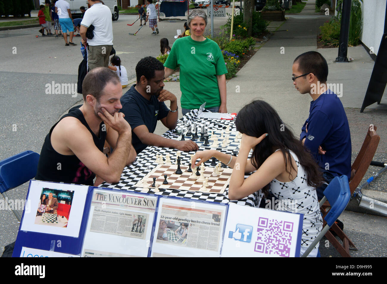 Young woman chess champion and people of different races playing chess outdoors on Main Street in Vancouver, BC, - Stock Image