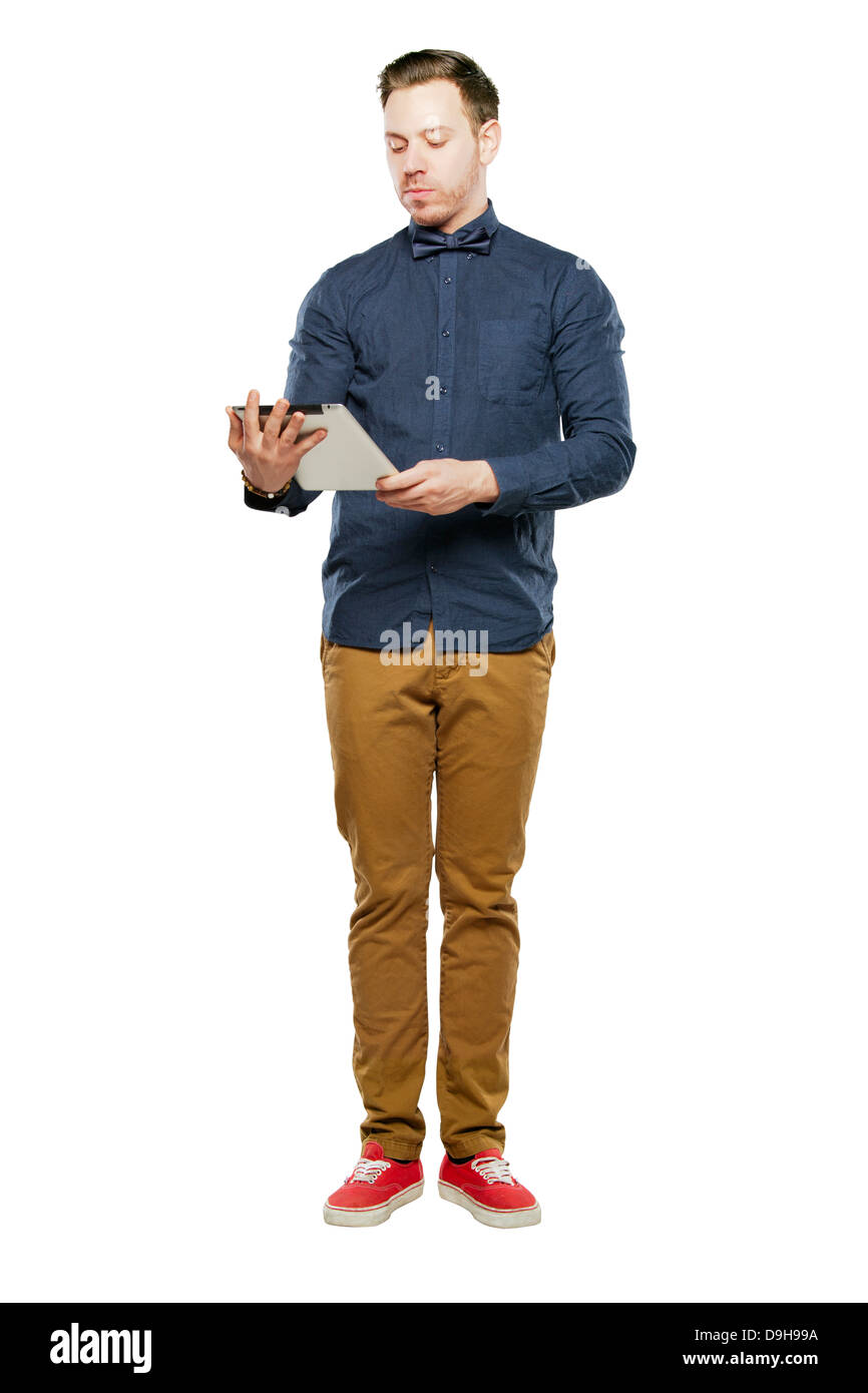 Hipster man in bow tie looking stylish using tablet - Stock Image