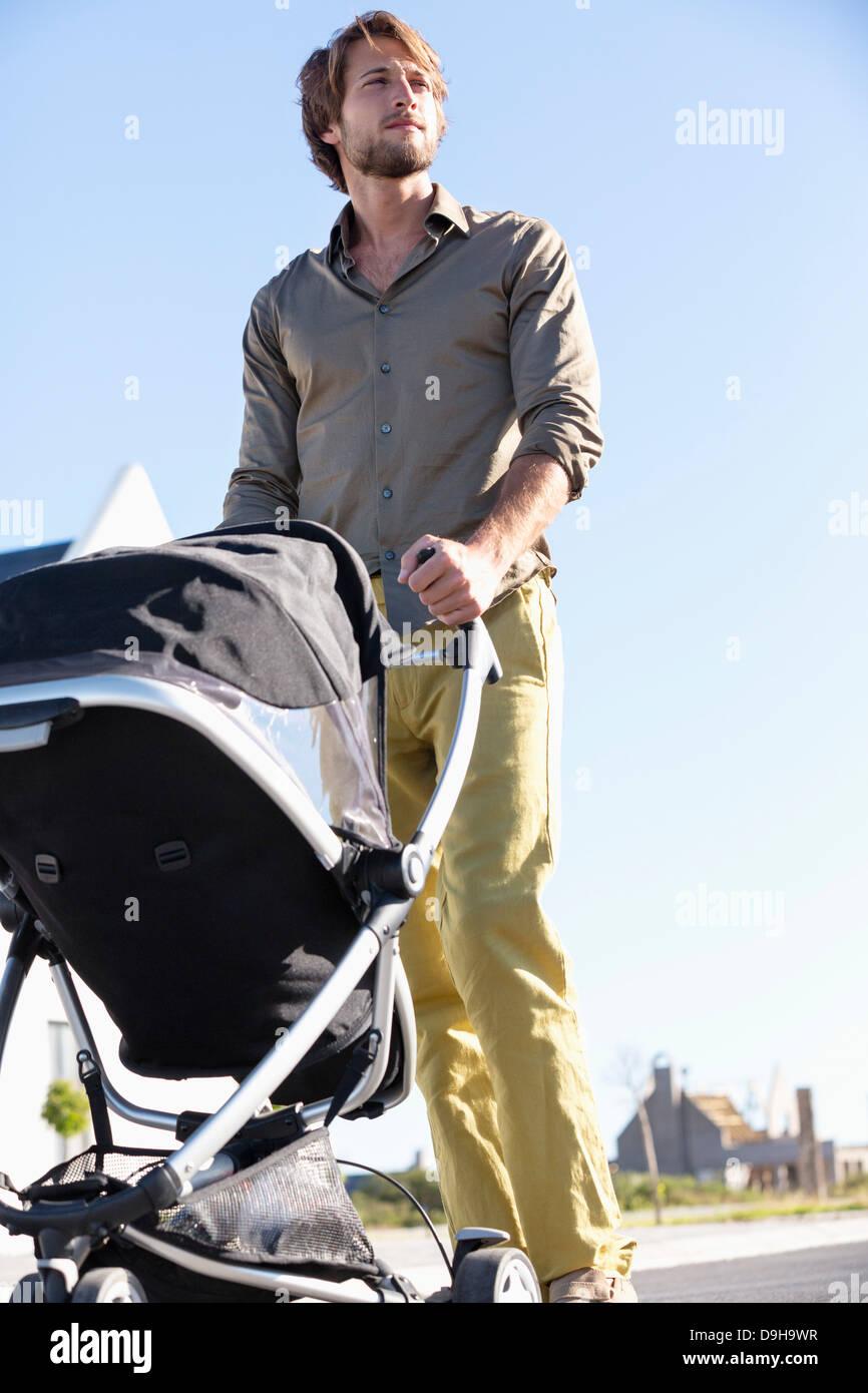 Man pushing a baby stroller - Stock Image