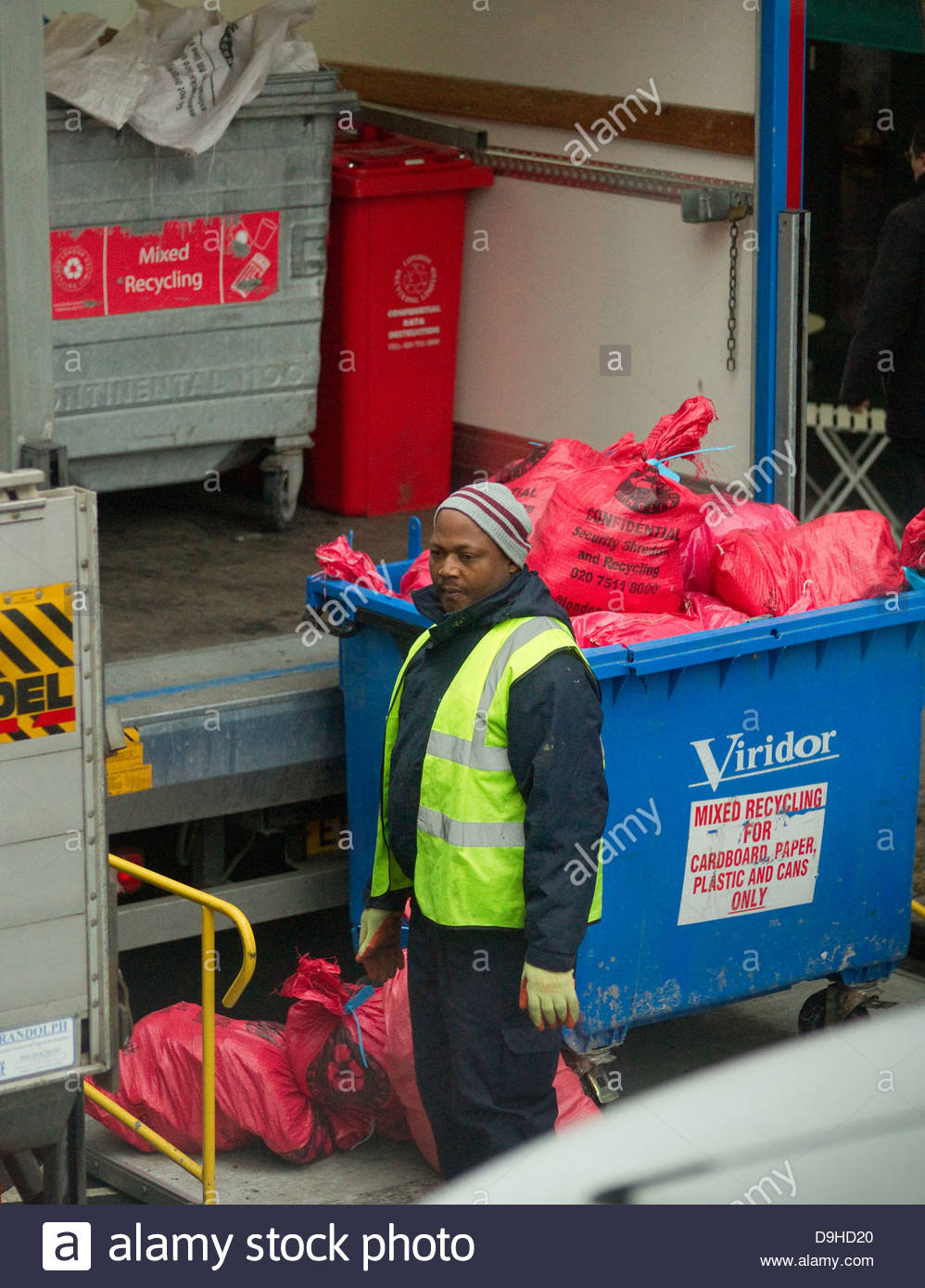 adult bags bins black collecting collection collects industrial industry lorry man recycles recycling refuse rubbish - Stock Image