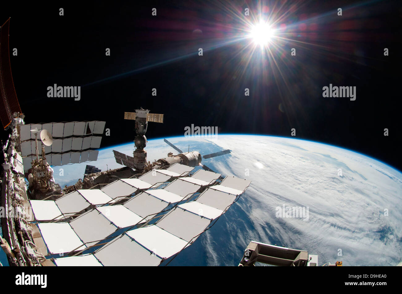 The bright sun, a portion of the International Space Station and Earth's horizon. - Stock Image