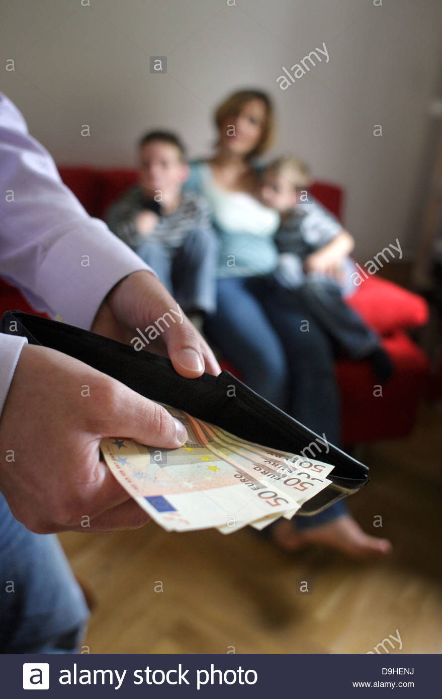 Man holding Euros with his family in the background - Stock Image