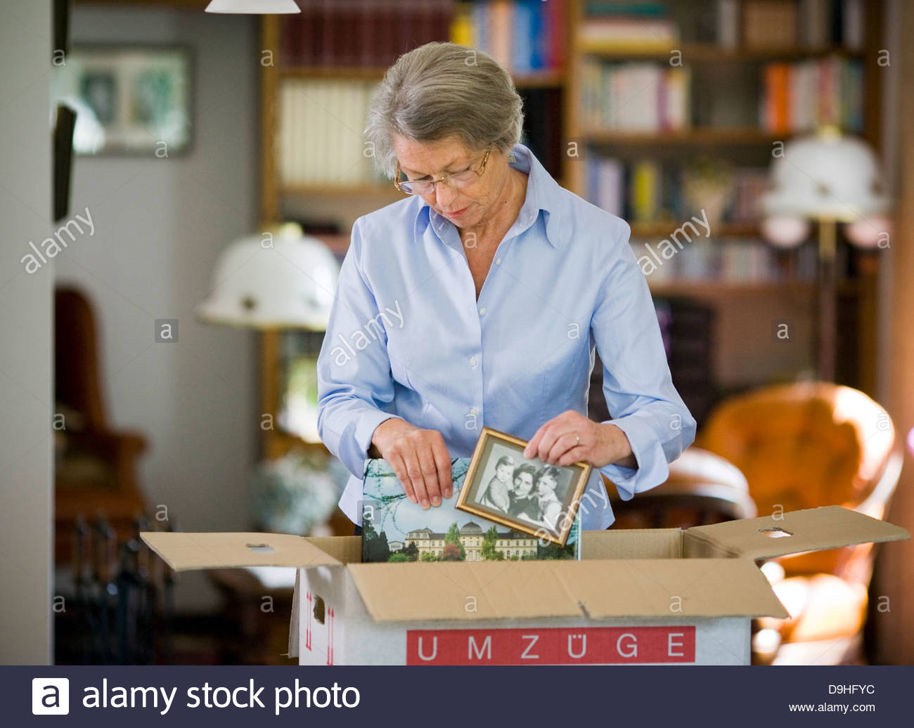 Senior woman packing picture frame in a cardboard box - Stock Image