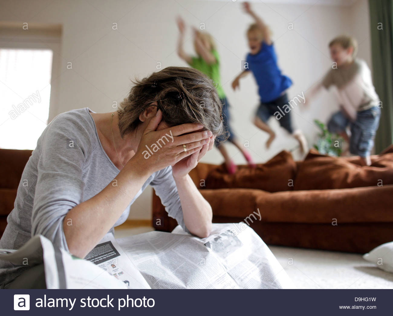 Frustrated woman with her children playing in the background - Stock Image