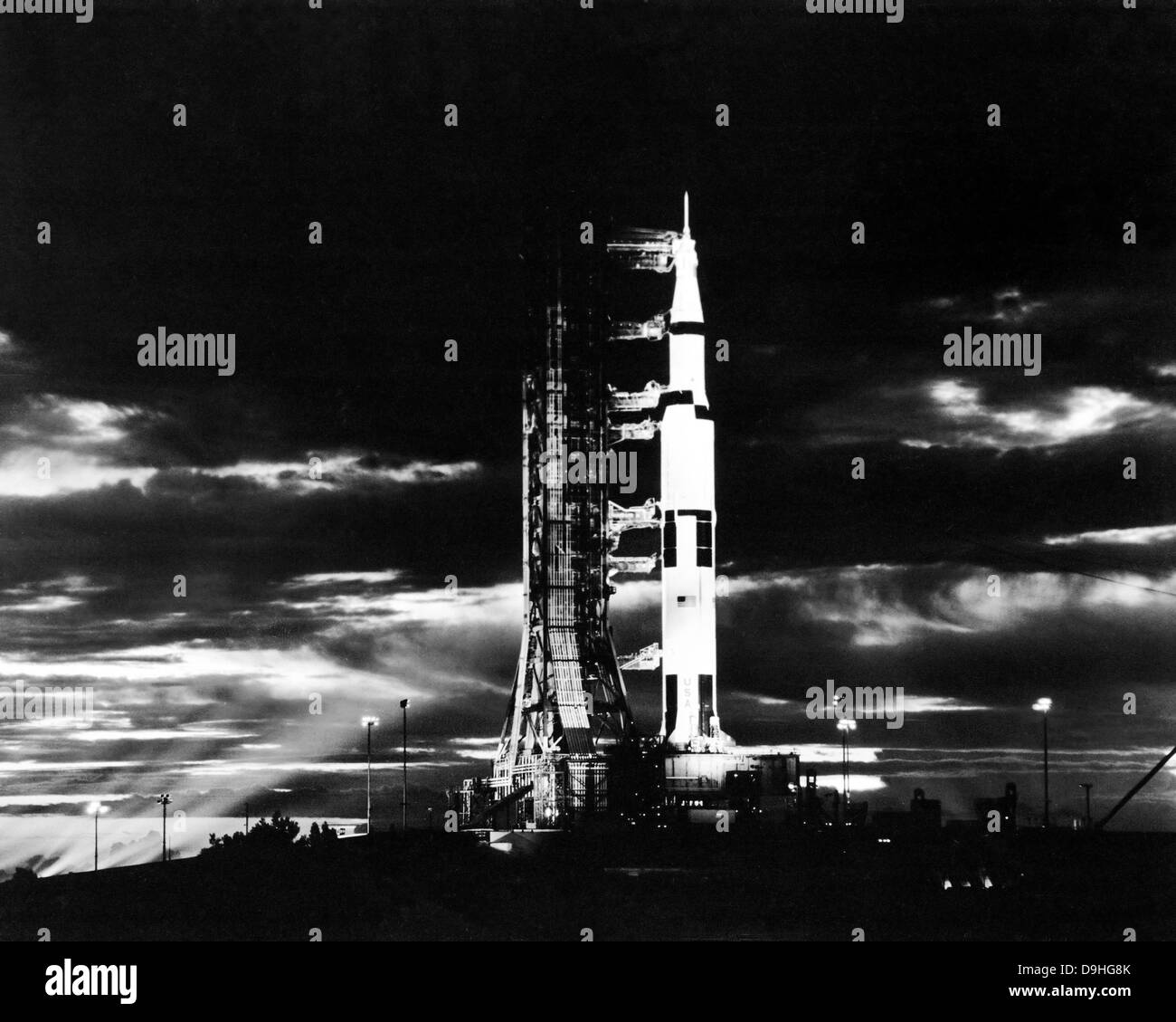 Searchlights illuminate this nighttime view of Apollo 17 spacecraft on its launchpad. - Stock Image