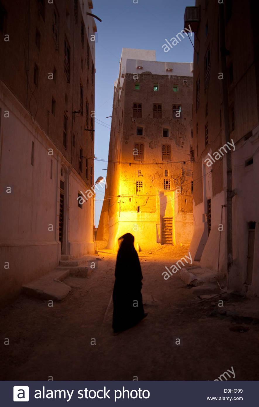 Woman walking in a street at night, Shibam, Hadhramaut, Yemen - Stock Image