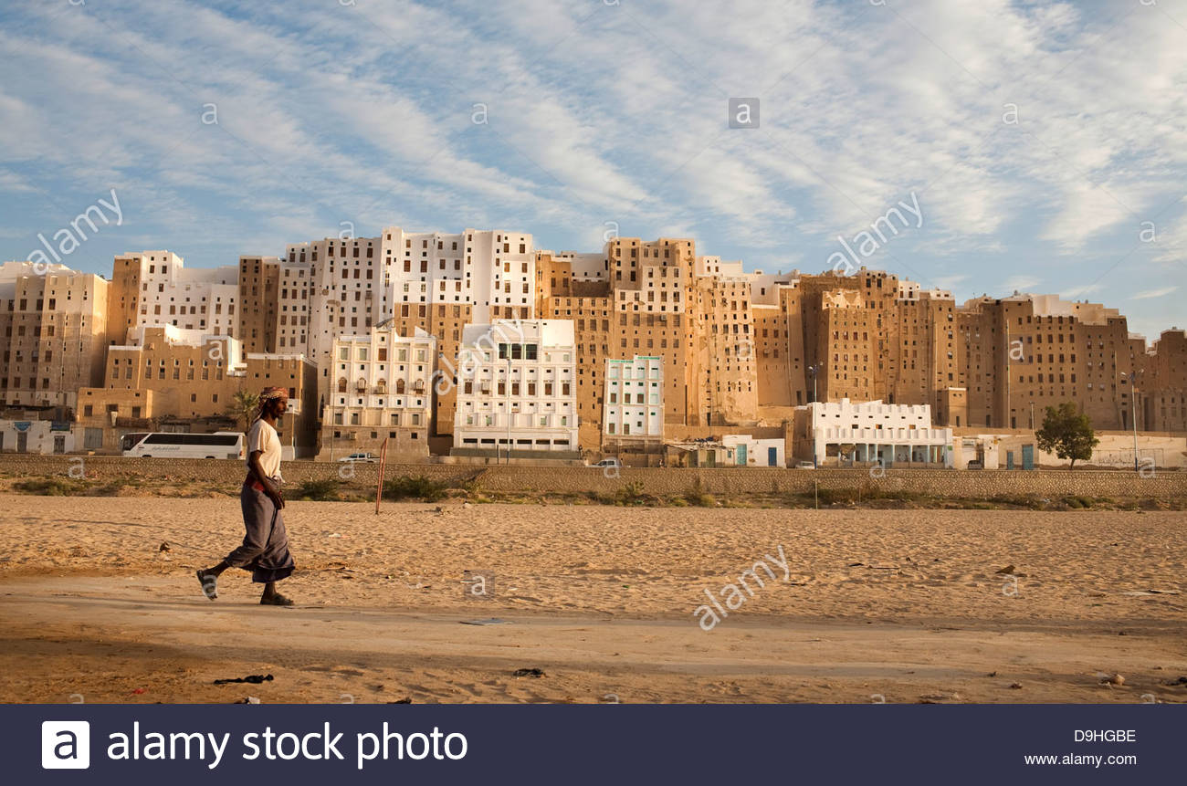 Man walking with a city in the background, Shibam, Hadhramaut, Yemen - Stock Image