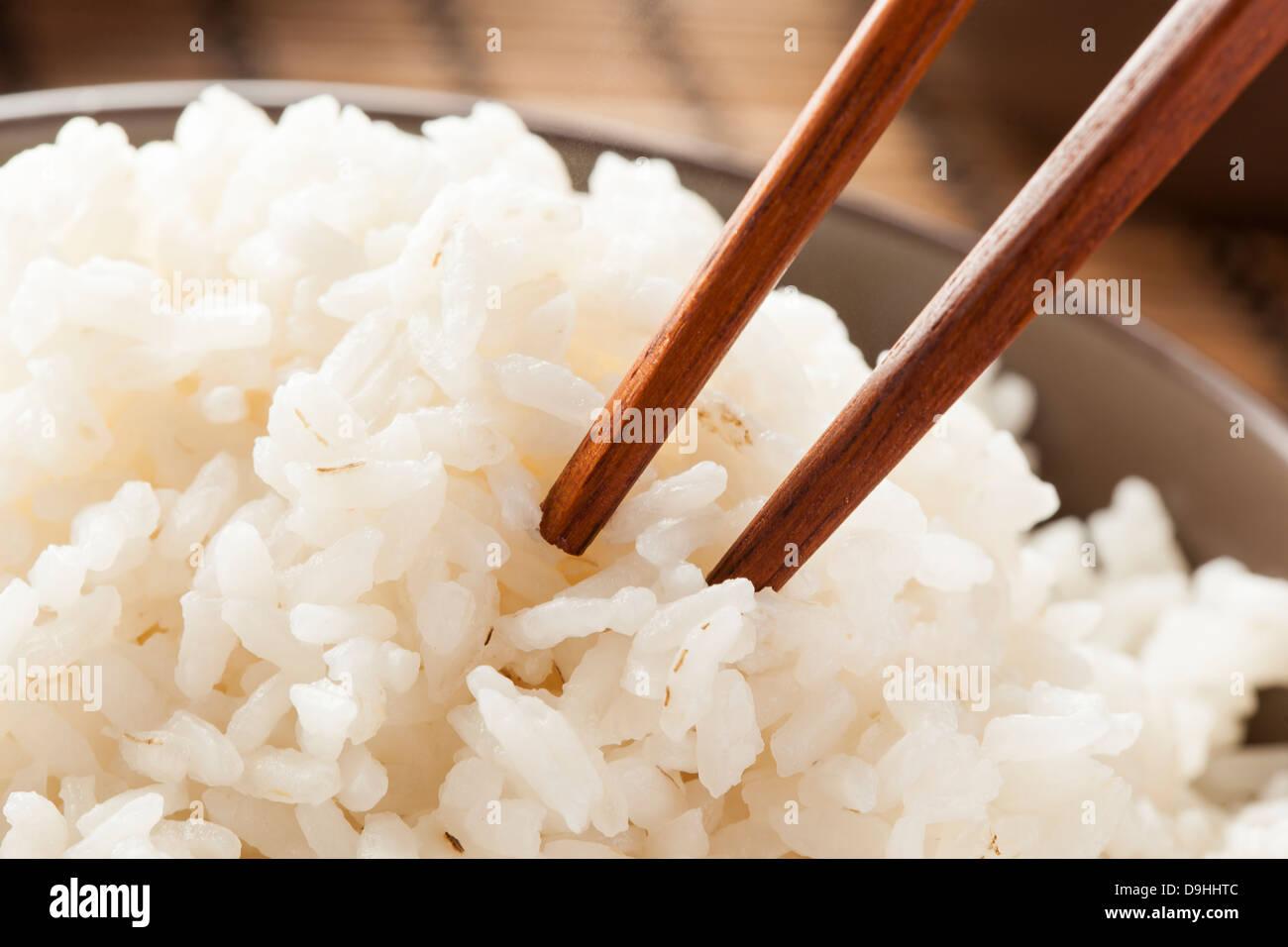 Bowl of Organic White Rice with chop sticks - Stock Image