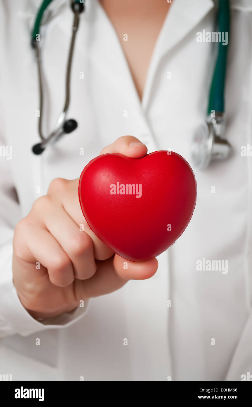 Red heart shape in a doctor's hand - Stock Photo