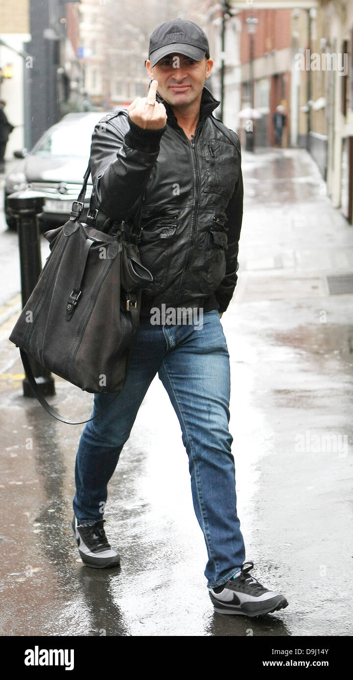 Louie Spence gives  the bird  finger gesture as he walks in the rain in  black leather jacket and baseball cap. London 9719a89ebb0