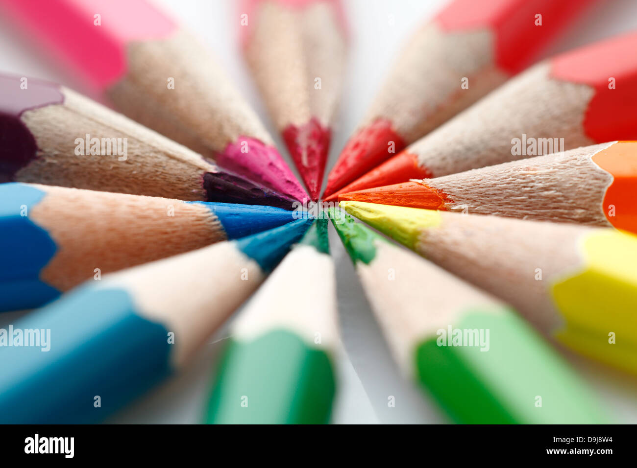Coloured pencils arranged to form a circle, meeting at the tips - Stock Image