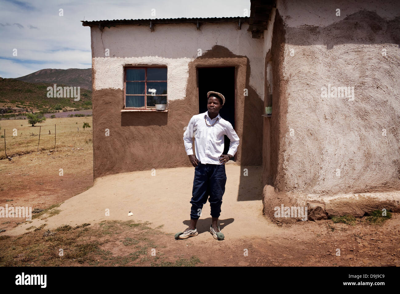 Young man recently returned from the city, stands proudly outside his his family home in rural Transkei, South Africa - Stock Image