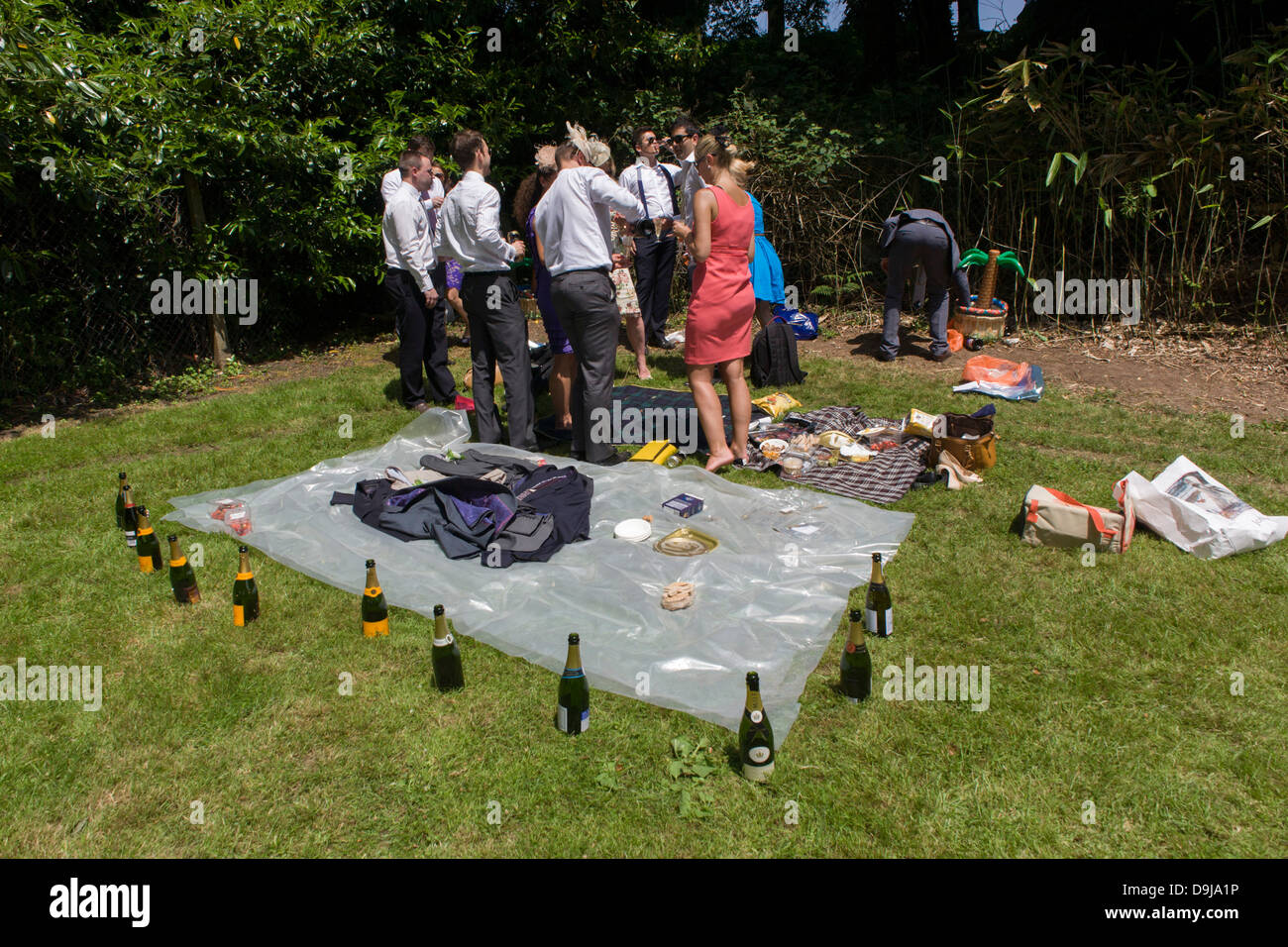 Wealthy punters with bottles of empty Champagne laid out enjoy a morning car park party on grass, hours before the - Stock Image