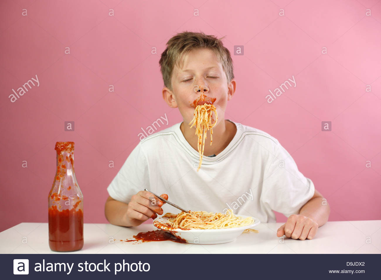 Boy eating spaghetti - Stock Image