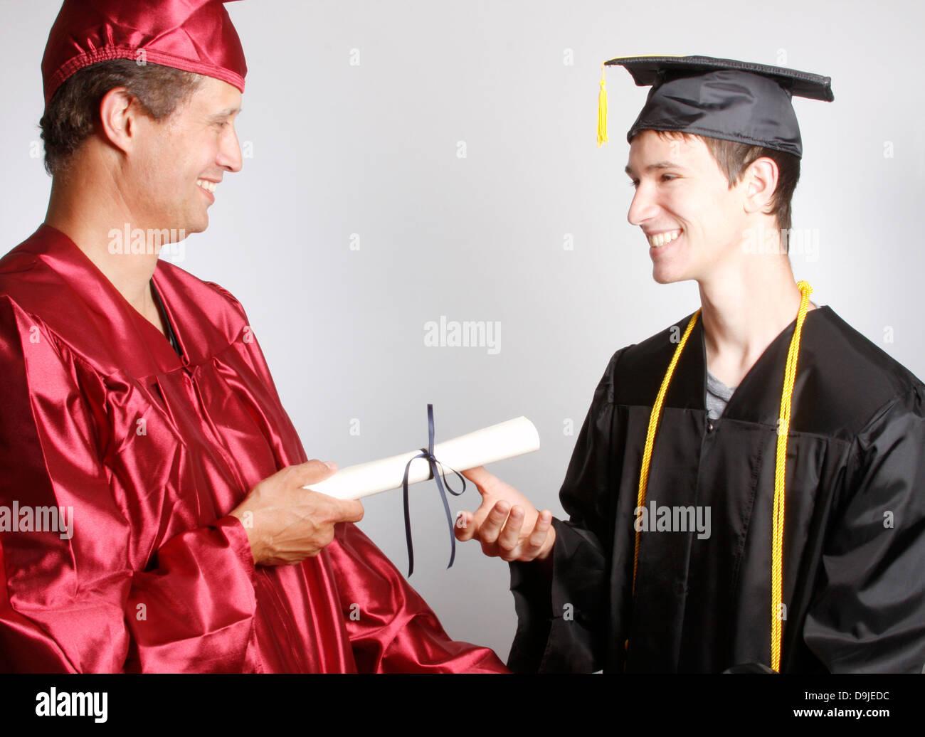 A Dean handing a graduate a diploma - Stock Image