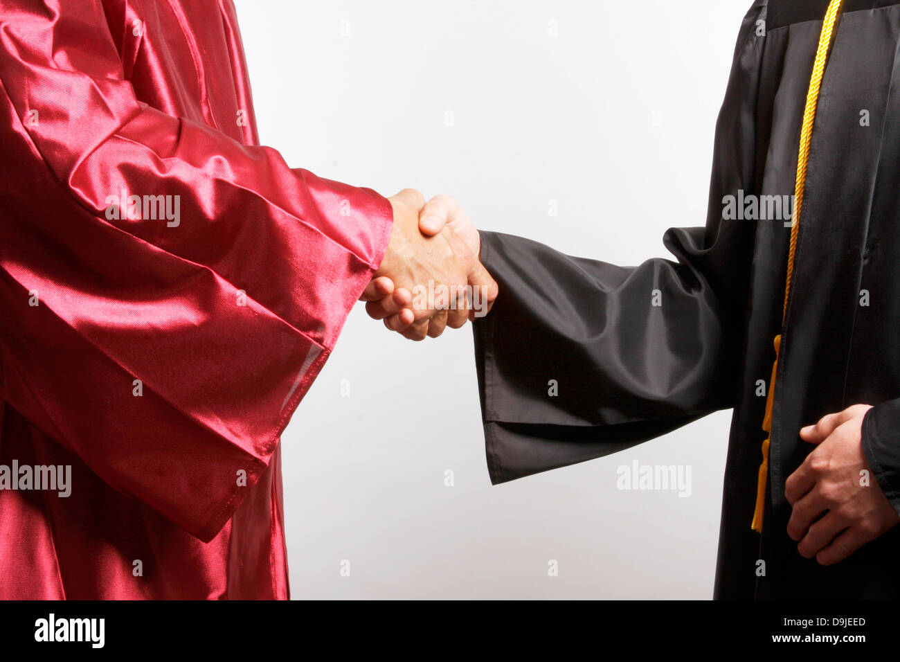 A Dean shaking hands with a graduate - Stock Image