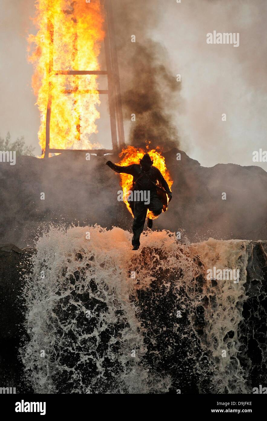 Lennestadt-Elspe, Germany. 20th June, 2013. A burning stuntman playing Ganoven Grinley jumps down a waterfall during - Stock Image