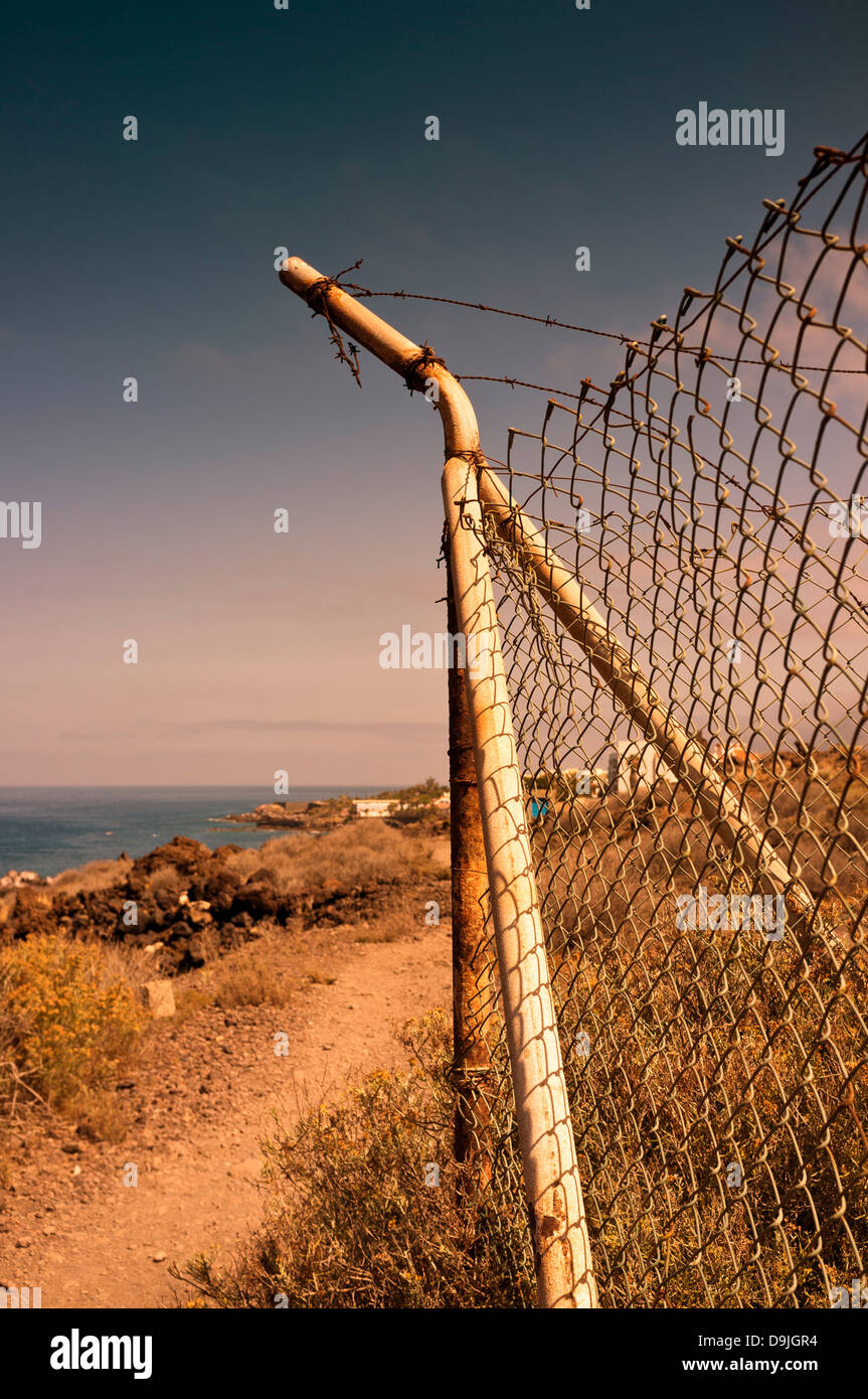 Corner post of chicken wire fence with broken strands of barbed wire above, on the coast, near Alcala, Tenerife, - Stock Image