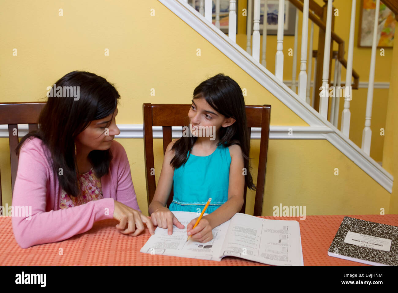 Mexican mother (45 year old) helps her Mexican-American 10 year old daughter with homework. - Stock Image