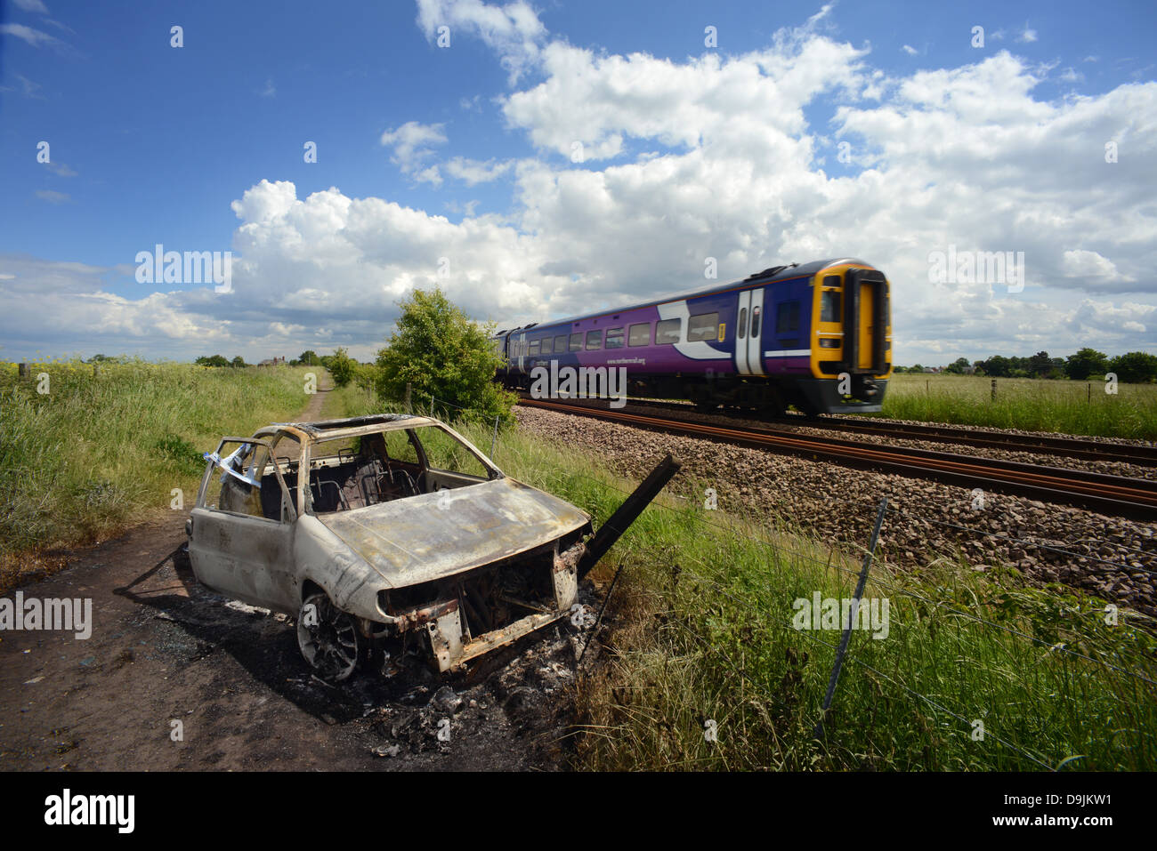 northern rail train passing burnt out and abandoned car leeds united kingdom - Stock Image