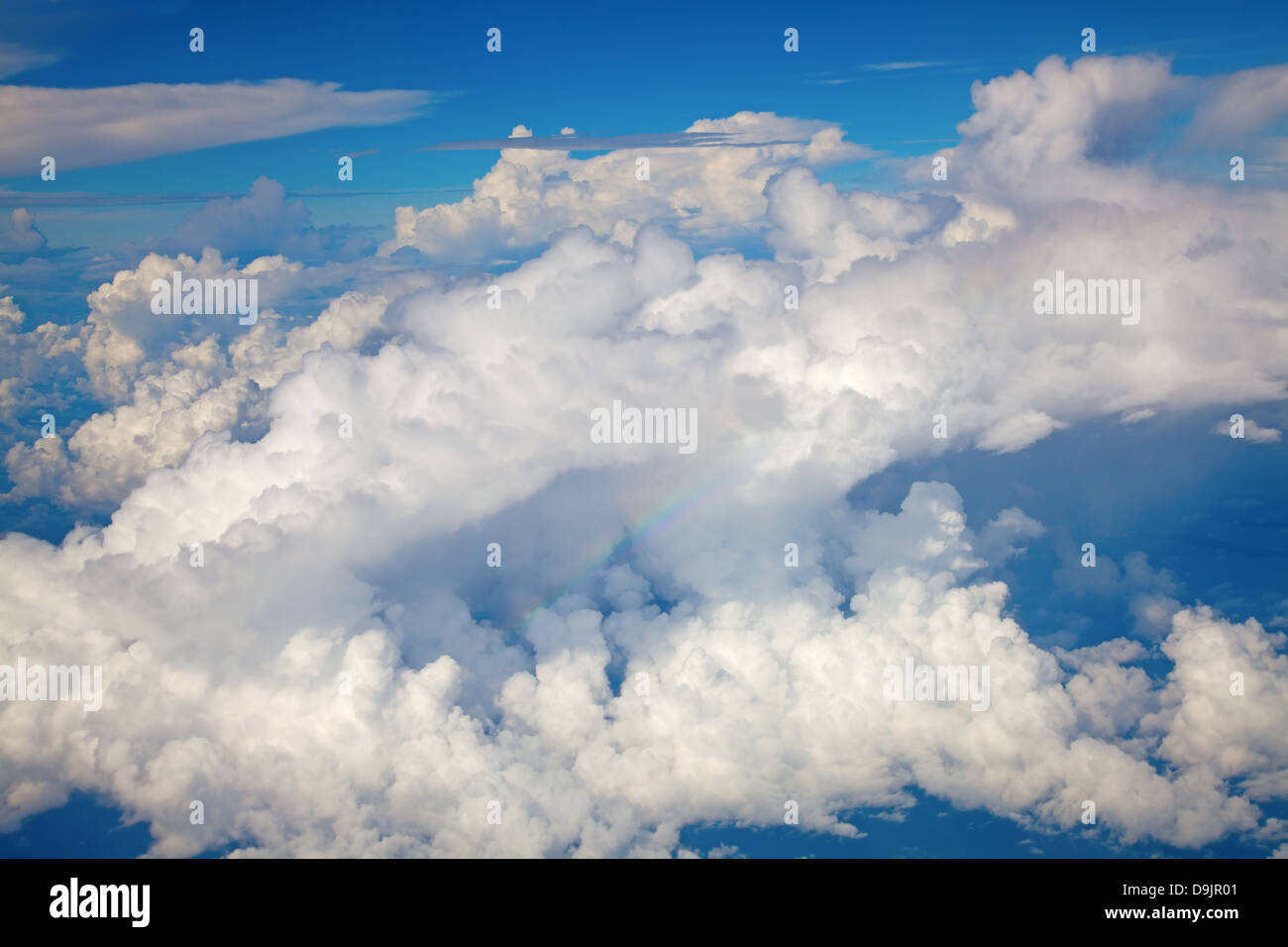 Beautiful cloudscape with fluffy cirrus clouds and rainbow - Stock Image