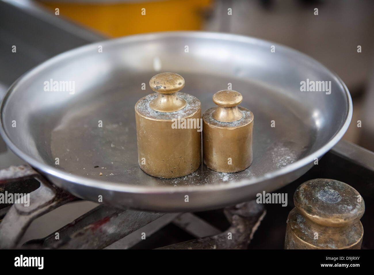 A set of antique weights on a scale used for measuring ingredients at the Caroppo Bakery, Specchia Gallone. - Stock Image