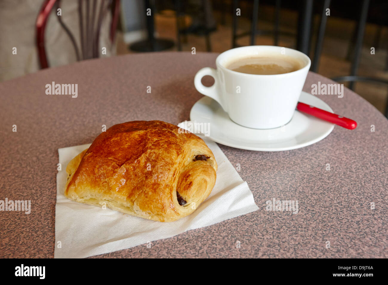 pain au chocolate and cafe au lait in a cafe bar in france - Stock Image