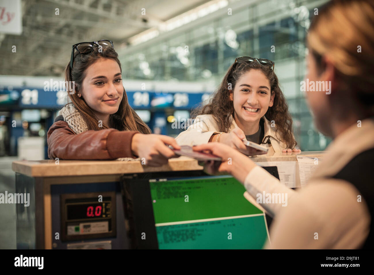 Two teenage girls at airport check in area - Stock Image
