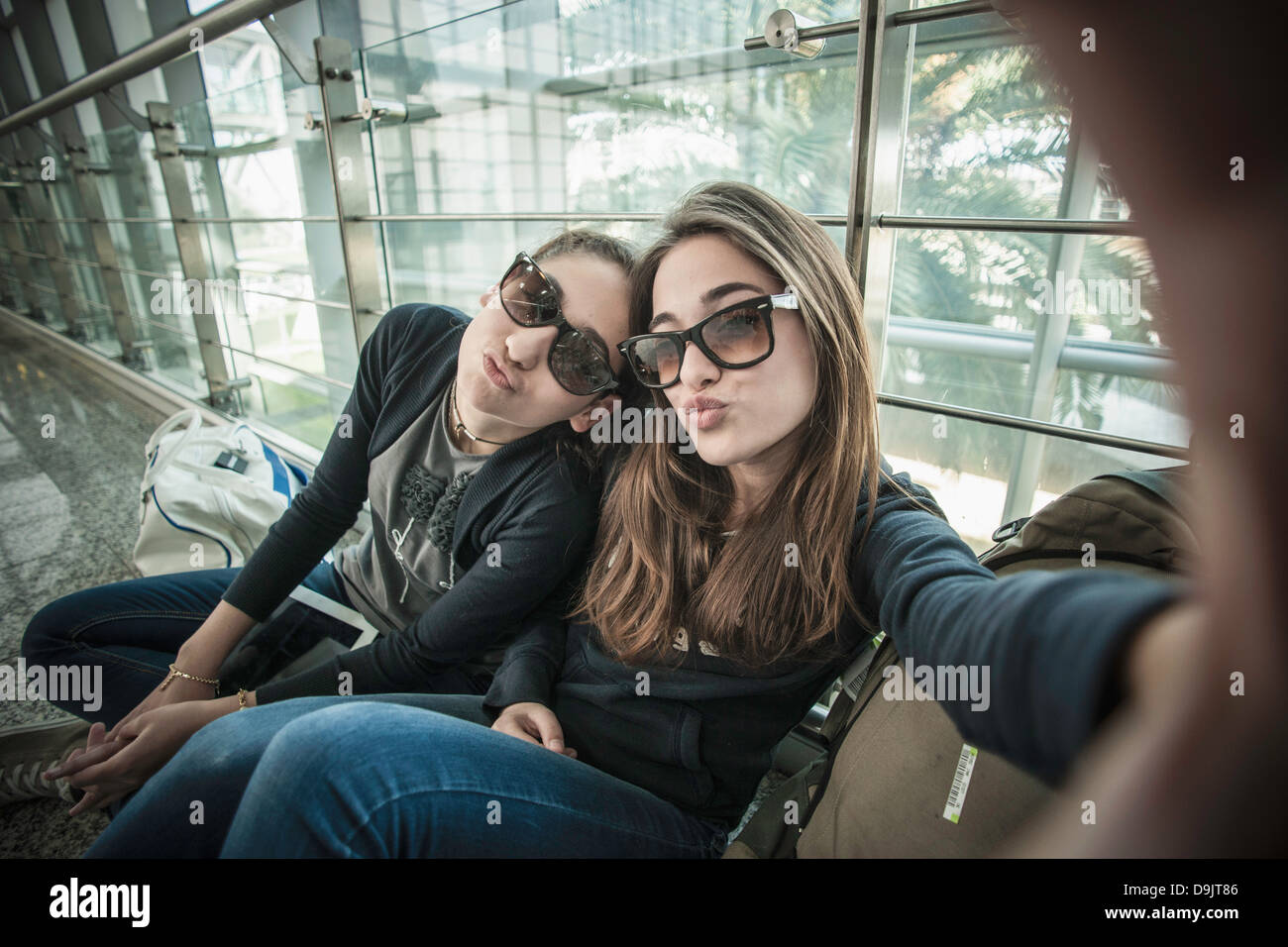 Two teenage girls posing to camera, photographing themselves - Stock Image