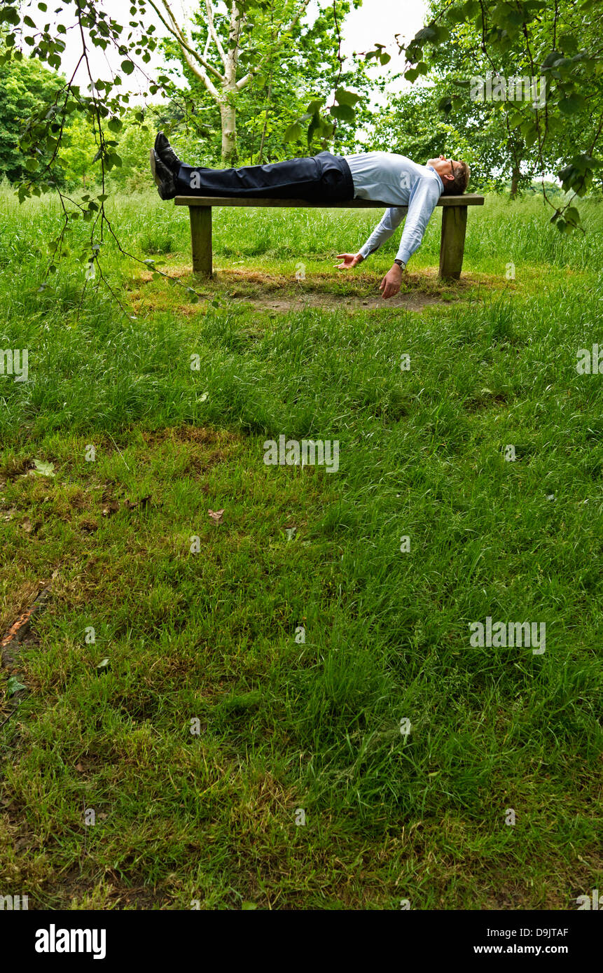 A businessman lies in the supine position on a wooden bench in Regent's Park, London. Portrait. - Stock Image
