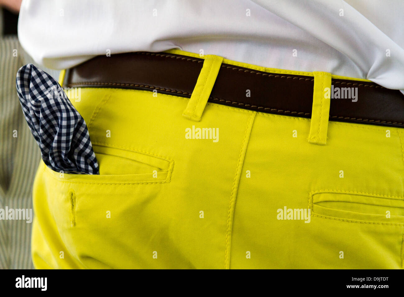 Detail of rear view of yellow pants with checkered handkerchief in pocket. - Stock Image