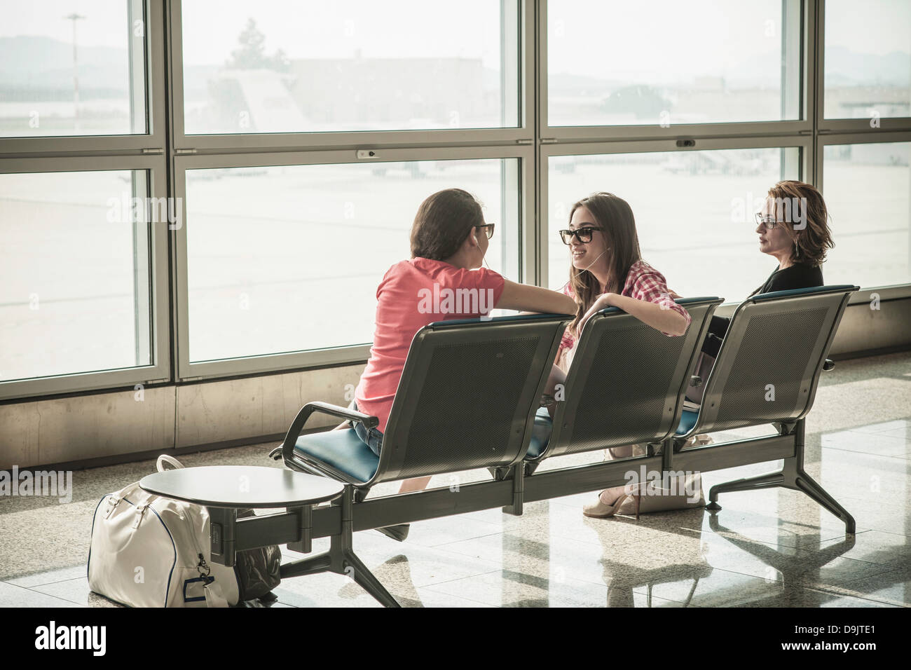 Two teenage girls and woman sitting in airport departure lounge - Stock Image