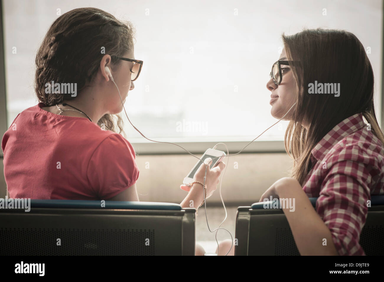 Two teenage girls wearing sunglasses listening to music Stock Photo
