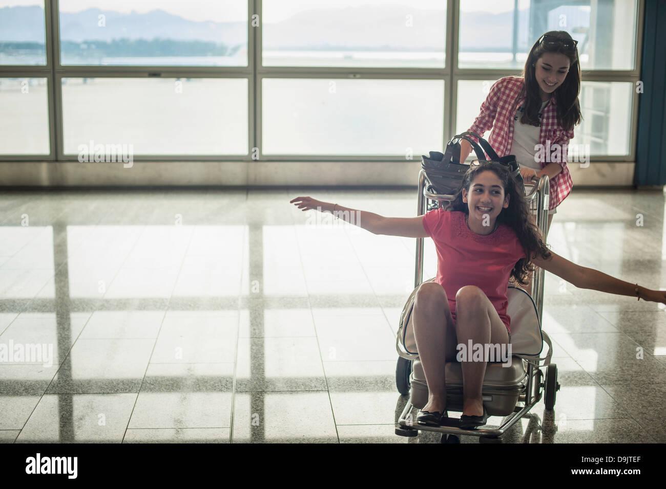 Teenage girl pushing friend on luggage trolley - Stock Image