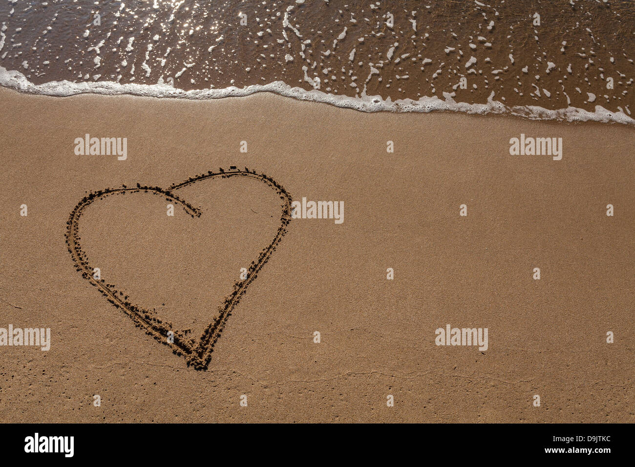Heart written on sand - Stock Image