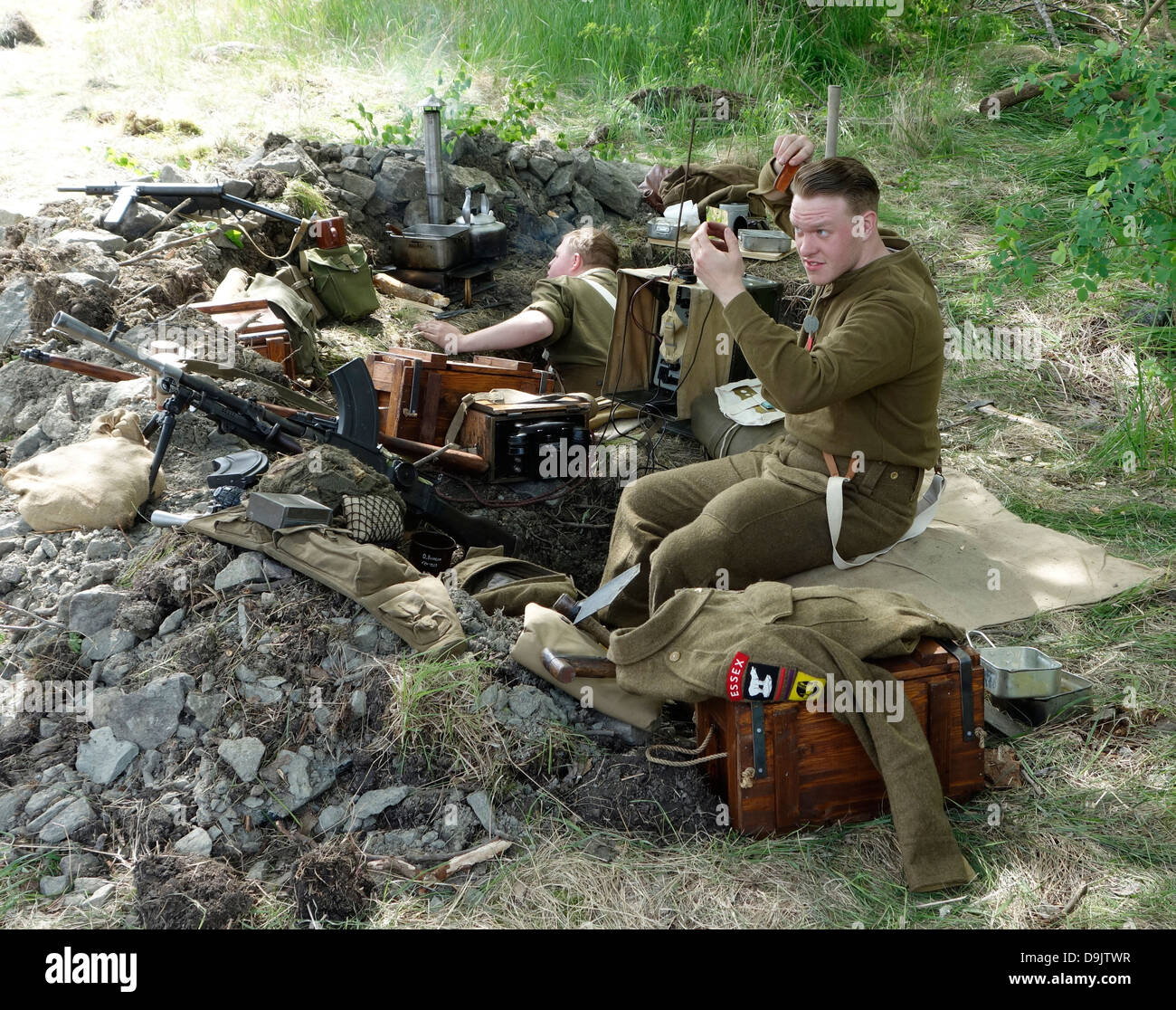 Historical re-enactment of ww2. British soldier sits in the trench and finds time to comb his hair . - Stock Image
